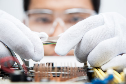 A researcher works on an electronics board