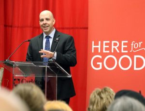 A photo of Carleton's President, Benoit Antoine Bacon, speaking at a podium with a red backdrop