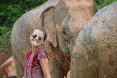 Image of student with an elephant while on an International Placement in Thailand