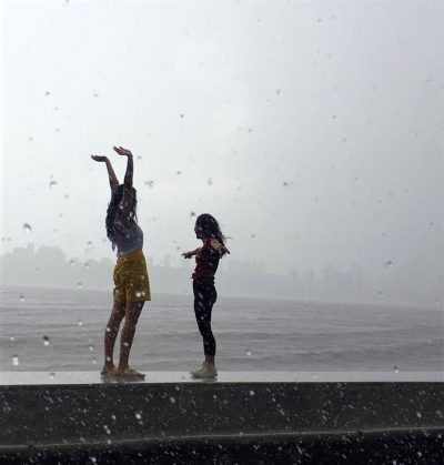 Image of Two children dancing in the Monsoon Rains in Mumbai India, photo taken by student on an International Placement