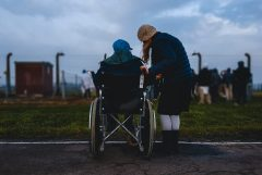 Caregiver and woman in wheelchair from behind in outdoor setting