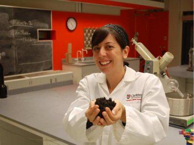 maria-derosa-in-her-lab-at-carleton-u-with-handful-of-soil