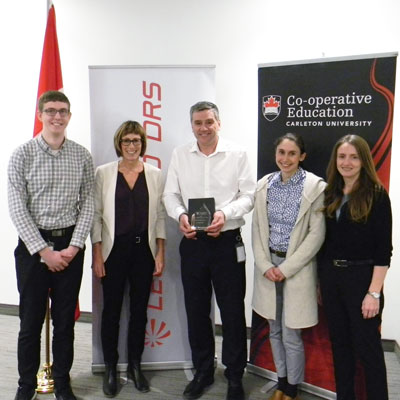 Paul-Young Davies holding the 2018 Co-op Employer of the Year Award, standing with two members of Carleton's Co-op staff and two Carleton co-op students at the Leonardo DRS office.