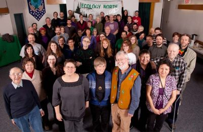A group of Ecology North supporters and members pose in front of an Ecology North sign.