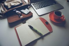 An open lined notebook on a desk with a laptop and orange coffee cup.