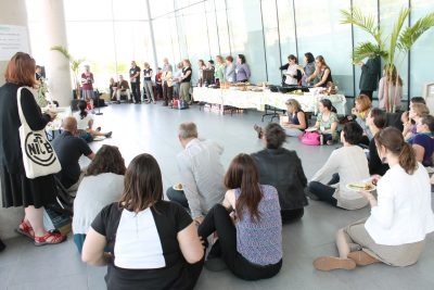 Conference attendees sit and stand in a bright open room while Cathleen Kneen speaks at a microphone.