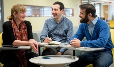 (Left to right) Carleton professor Patricia Ballamingie, Jason Garlough of the Ottawa Eco-Talent Network, and doctoral research assistant Michael Lait sit around a table discussing community engagement in anticipation of Carleton's fourth annual Community Engagement Event on Feb. 24, 2016.