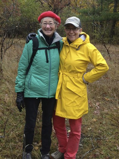 Cathleen Kneen and Abra Brynne stand huddled together, bundled in winter jackets, enjoying an outdoor hike.