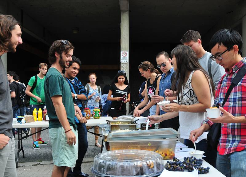 Students gather around a table full of food from the Carleton Food Collective.