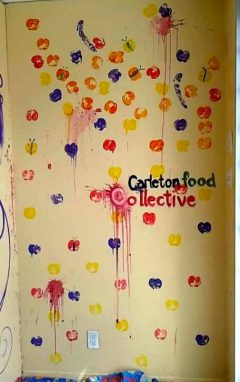 A wall covered in self-painted apple prints at the Carleton Food Collective.