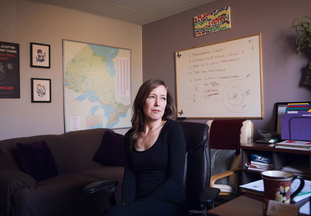 Portrait of Sunny Marriner, Executive director of the Ottawa Rape Crisis Centre, as she sits in her office surrounded by a couch, desk, and white board.