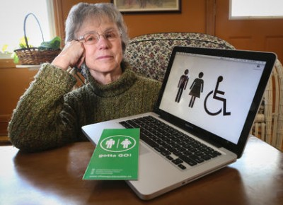 Joan Kuyek, Chair of the GottaGo! campaign, poses beside an open computer with a bathroom sign as its desktop image.