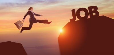 """A woman in business attire and holding a briefcase, leaping between one rock and another rock with the text """"job"""" resting on it."""