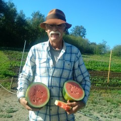 Glenn Flett of LINC, holds a ripe watermelon cut in half at Emma's Acres.