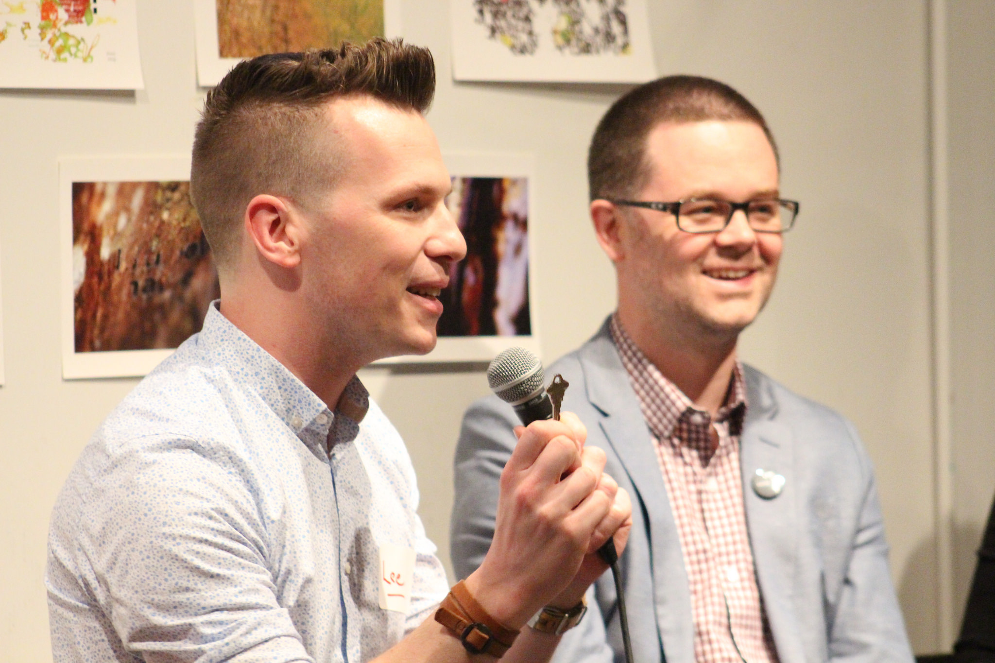 Lee Rose speaking into a microphone while standing beside an out-of-focus, smiling man.
