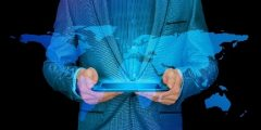 A person in a business suit holding a tablet out of which is floating a holographic map of the world.