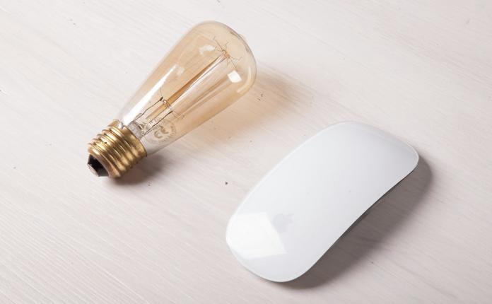 A light bulb beside a white Macintosh computer mouse.