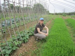 Steffanie Scott, a CFS Hub collaborator, crouches near some vegetables she is growing.