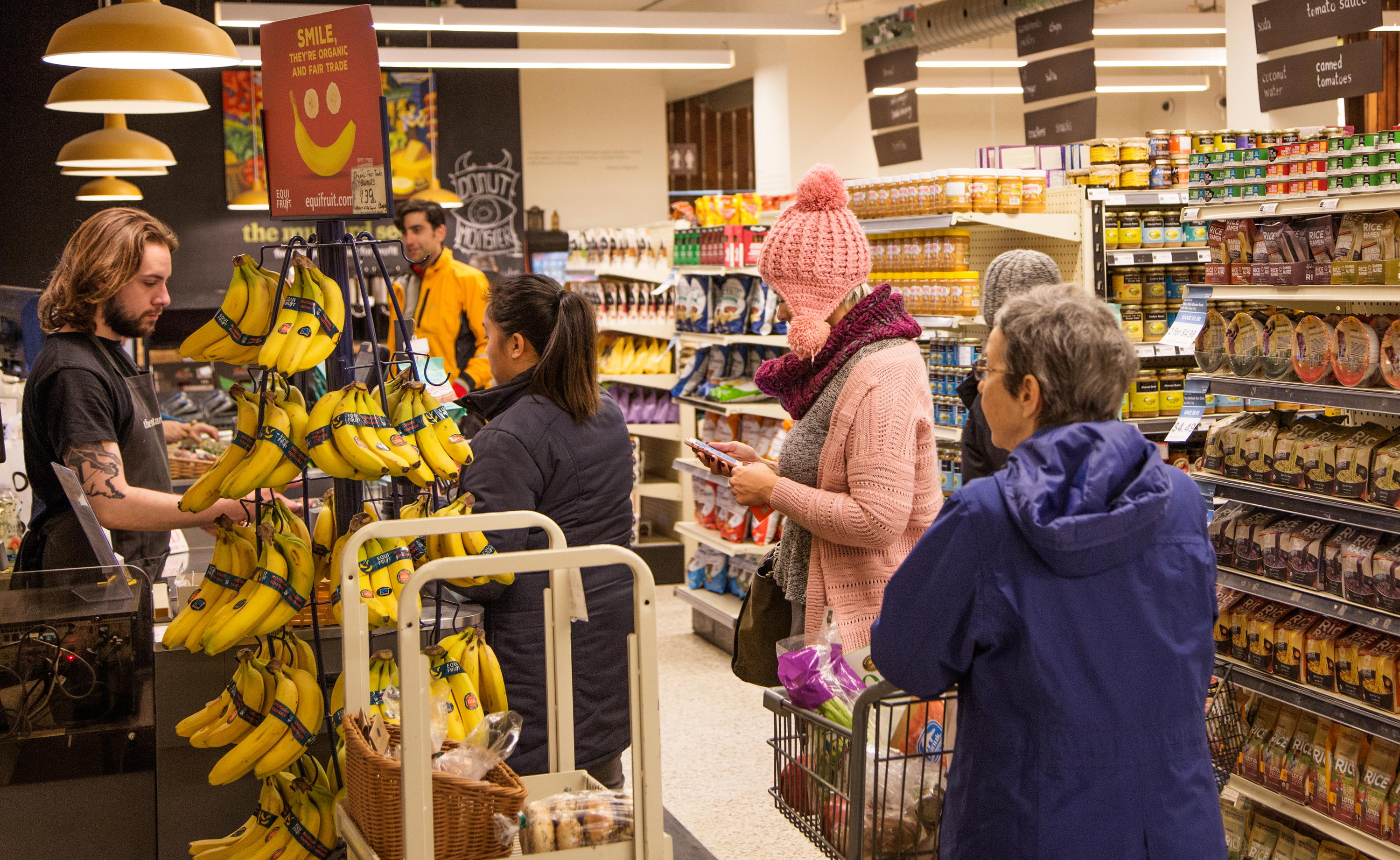 An employee serves customers buying groceries at The Mustard Seed
