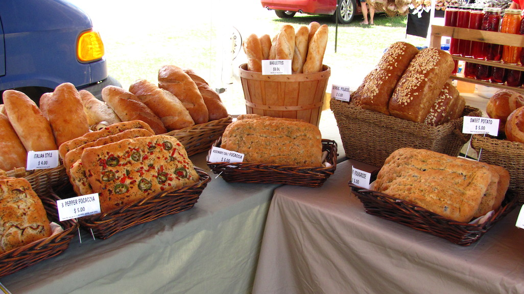 Freshly baked loaves of bread arranged in a semi-circle on a farmers' market table.