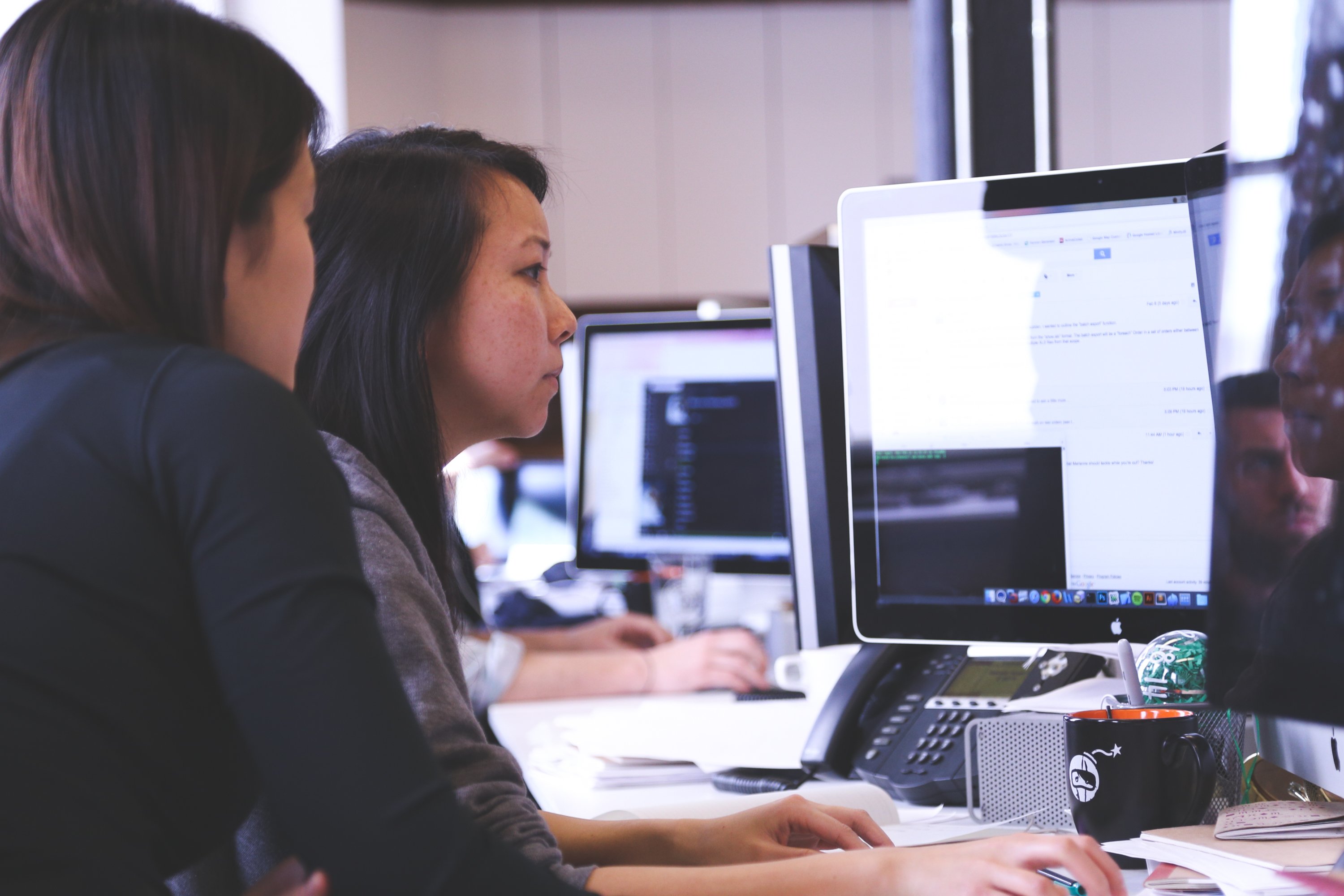 Profile shot of two women working together at a computer.