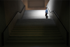 A young woman waits at the top of a long dark staircase.