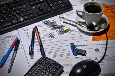 A desk scattered with paper clips, financial documents, a calculator, and a teacup.