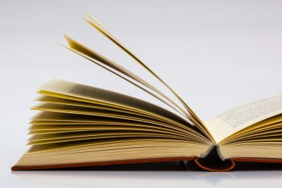 A book laying on a table with some pages floating up as the book is opened.