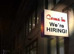 "A sign above a business reads ""Come in, we're hiring""."