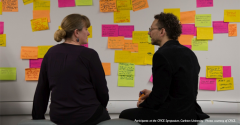 2 people sitting in front of a brainstorming board