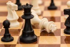 A close up shot of a black chess queen on a chess board in front of a toppled white chess king.
