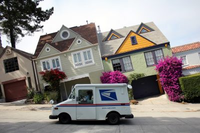 A picture of a mail truck parked on a hill with houses in the background. The picture is taken with the car aligned horizontally instead of the houses so the houses look as if they are slanted to the left.