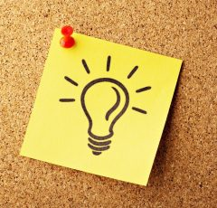 A cartoon of a lit lightbulb drawn on a yellow sticky note pinned to a cork board.