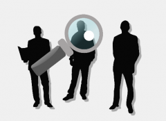 Three male business figures stand behind a magnifying glass.