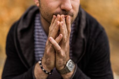 A man holding his hands together in a prayer position.