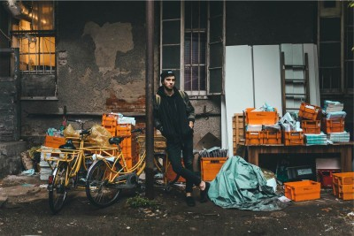 A man stands in an alley in front of grocery carts full of his life's possessions.
