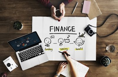 """Two people sit around a giant paper with the word """"finance"""" across it, and images outlining the next steps from funding to growth."""