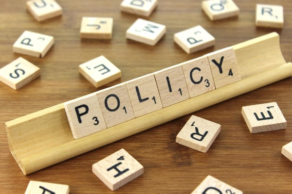 """Scrabble tiles arranged to form the word """"Policy""""."""