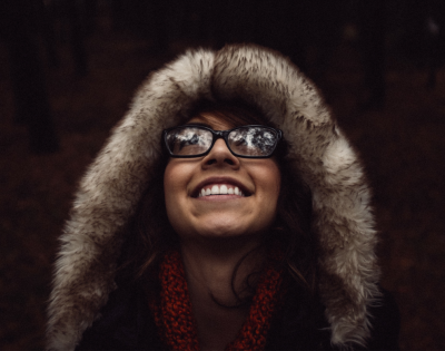 A woman wearing a fur hood and glasses looks up toward an unseen object outside of the camera's view. She is smiling.