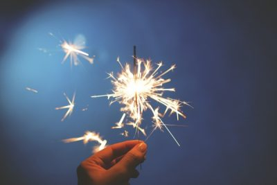 A hand holds up a lit sparkler.