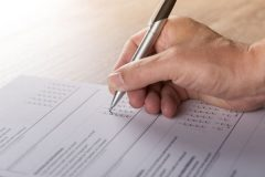 A man's hand holding a silver pen and completing a questionnaire.