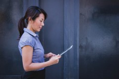 A woman works on an ipad.