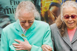Two senior women walking and holding each other by the arm