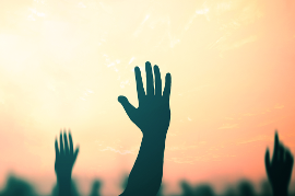 Profiles of multiple hands raised against sky
