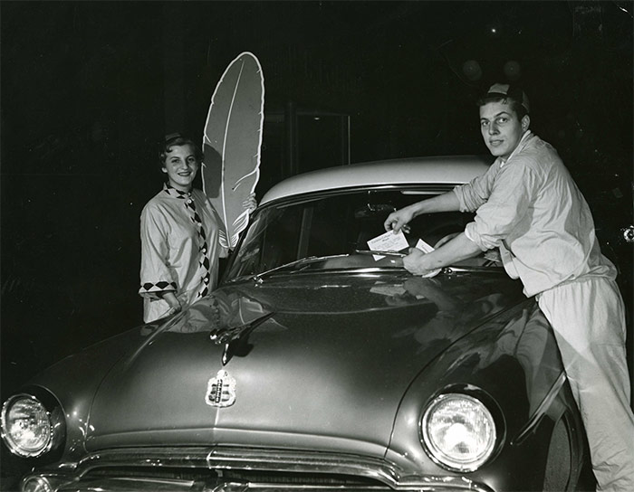 Red Feather Club members Jacqueline Aronson and John Redfern place flyers on cars for the Red Feather Campaign during Frosh Week, 1954. Library Special Collections fonds.