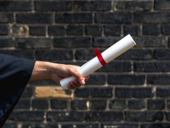 student holding out diploma in front of brick wall