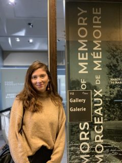 Student with banner of co-curated exhibition