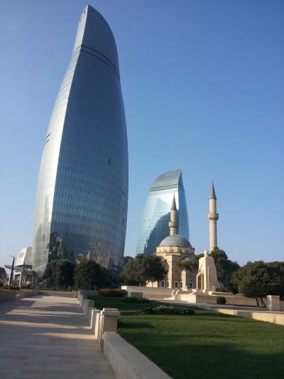 The Shahidlar Mosque is eclipsed by the Baku Flame Towers in Baku, Azerbaijan