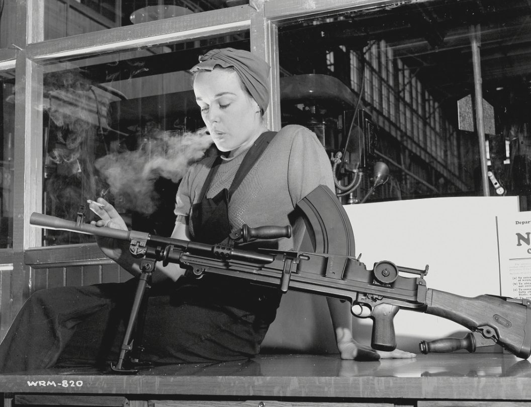 """Unknown photographer. Veronica Foster, an employee of John Inglis Co. Ltd. and known as """"The Bren Gun Girl"""" posing with a finished Bren gun in the John Inglis Co. Ltd. Bren gun plant, Toronto. 10 May 1941. Contemporary print from vintage negative. National Film Board of Canada. Photothèque / Library and Archives Canada e000760453."""