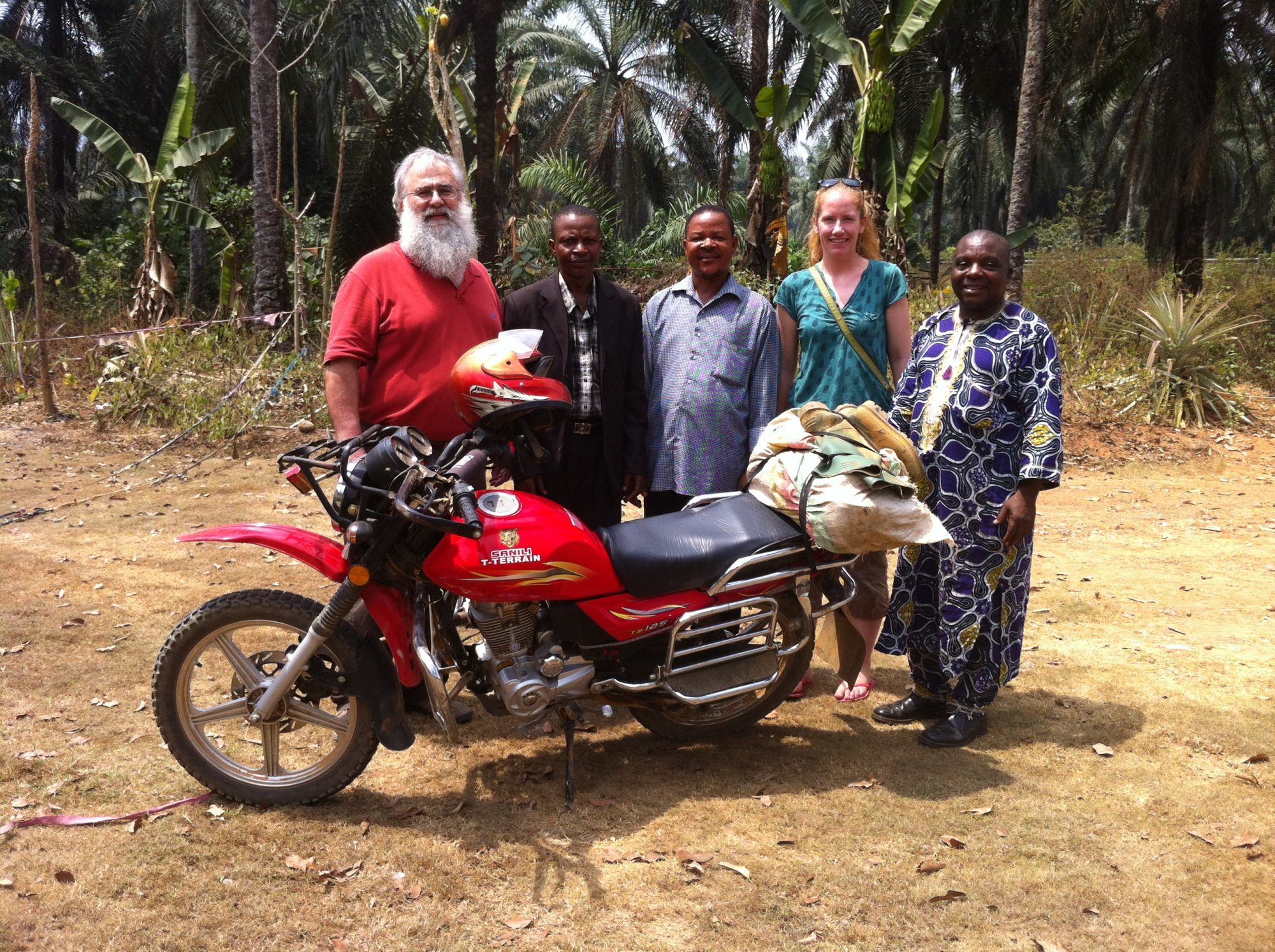 Professor Mike Brklacich beside a motorcycle in Cameroon, Lake Barombi.